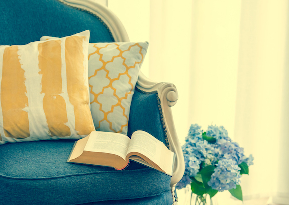 Cozy armchair with open book and decorative pillows. Interior and home decor concept. Toned image