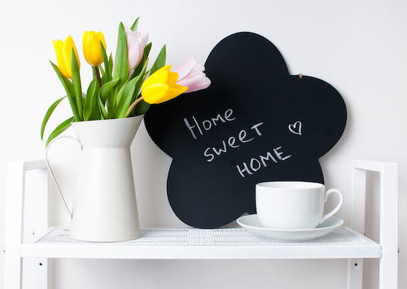 home interior decoration: a bouquet of tulips in a jug, cup and saucer, and chalk board on the white shelves