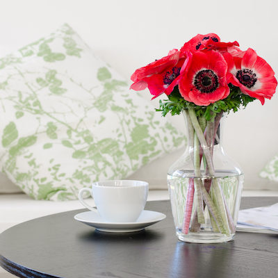 vase of red flowers in modern white living room - home decor
